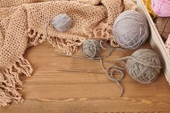 Brown knitted plaid and yarn on wooden background royalty free stock photo