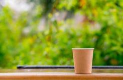 Brown-KraftpapierKaffeetasse auf dem Frühlingsgrün-Bäume backgroung Bereiten Sie vor, um zu gehen oder Kaffee wegzunehmen stockbilder