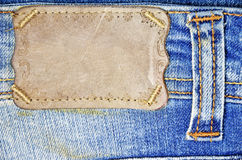 Brown label on blue jeans Stock Images
