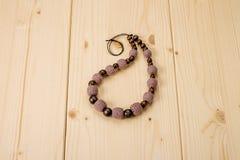 Brown lavora all'uncinetto le perle fatte a mano su una tavola di legno leggera Fotografia Stock