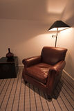 Brown leather armchair in a luxury apartment. Luxury brown leather arm chair in a modern apartment with striped carpet and lamp in the background Royalty Free Stock Photos