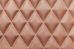 Brown leather background and texture stitched with white diamond-shaped threads as a pattern for the interior of the vehicle`s royalty free stock photos