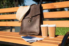 Brown leather bag with hat, passport with tickets, map and paper cups on wooden bench Royalty Free Stock Photo