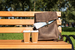Brown leather bag with map and disposable coffee cups on wooden bench Stock Photo