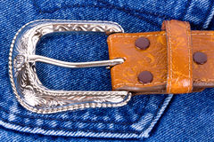 Brown leather belt on blue jeans. Royalty Free Stock Image