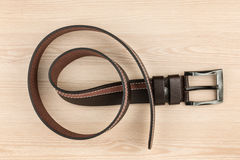 Brown leather belt with buckle lying on a wooden surface Royalty Free Stock Photo