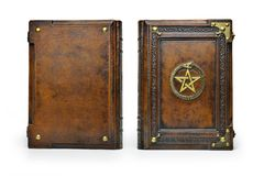 Brown leather book cover with gilded pentagram and the Ouroboros symbol, surrounded with deeply embossed frame and metal corners royalty free stock image
