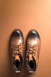 Brown leather boots over brown background,above view with copy s Royalty Free Stock Photos