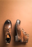 Brown leather boots over brown background,above view with copy space for text or other Royalty Free Stock Photography