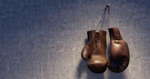 Brown leather boxing gloves hanging on grungy concrete wall Royalty Free Stock Photography