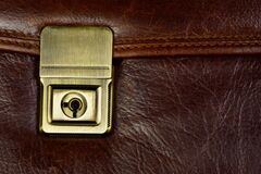 Brown leather briefcase and clasp lock. Briefcase is a rectangular bag for carrying and storing papers, notebooks, books, and