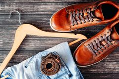 Brown leather casual shoes, jeans and belt on dark wooden background top view. Fashion concept Stock Photos
