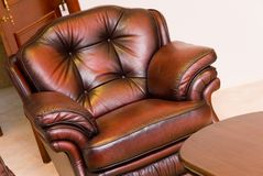 Brown leather chair. Chocolate brown leather chair set in a formal lounge room setting with a fire place also in the room Stock Image