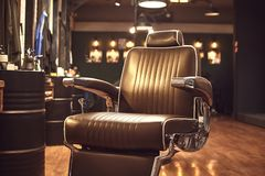 Brown leather chair in barbershop. Loft style royalty free stock photos