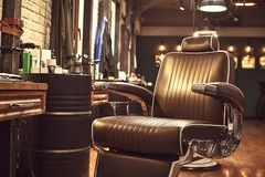 Brown leather chair in barbershop. Loft style royalty free stock photography