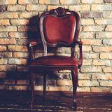 Brown leather chair in the room against brick background, toned Royalty Free Stock Images