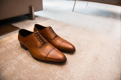 Brown leather classic male shoes on the floor.  Royalty Free Stock Image