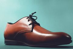 Brown leather executive shoes. Over blue Royalty Free Stock Image
