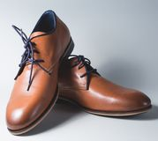Brown leather executive shoes. Over grey Royalty Free Stock Images