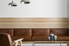 Brown leather furniture with wooden framework. Front view on brown leather sofa with wooden framework in modern loft room. 3D rendering Royalty Free Stock Photo
