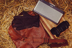 Brown Leather Gloves Beside Bose Speaker Dock and Black Dslr Camera Place on Red Leather Messenger Bag Stock Image