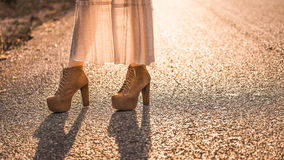 Woman Brown leather high heel shoes. Brown leather high heel shoes on a road at sunset Royalty Free Stock Photos