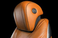 Brown leather interior of the luxury modern car. Perforated orange leather comfortable seats with stitching isolated on black back. Ground. Modern car interior royalty free stock images