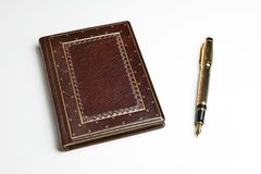 Brown leather journal with the posted golden fountain pen on the side royalty free stock photography