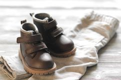 Brown leather kids shoes and denim pants on wood backdrop Stock Images