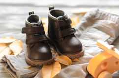 Brown leather kids shoes and denim pants, yellow leafs and toy c Royalty Free Stock Photography
