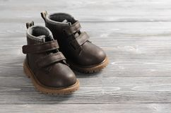 Brown leather kids shoes on wood backdrop Stock Photography