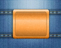 Brown leather label on blue jeans background Stock Images