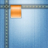 Brown leather label on blue jeans background Royalty Free Stock Photos