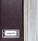 Brown leather magazine holder and magazines. Royalty Free Stock Photos