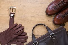 Brown leather men`s accessories on wooden desk. Brown leather gloves with belt, shoes and bag Stock Photo