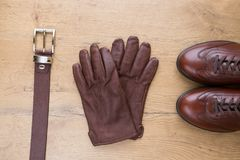 Brown leather men`s accessories on wooden desk. Brown leather gloves with belt and shoes Royalty Free Stock Photos