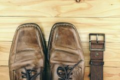 Brown leather men`s shoes and belt on a wooden board Royalty Free Stock Images