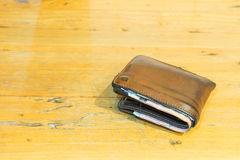 Brown leather men's wallet with bank notes on brown wood texture Royalty Free Stock Photos