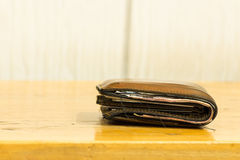 Brown leather men's wallet with bank notes on brown wood texture Stock Images