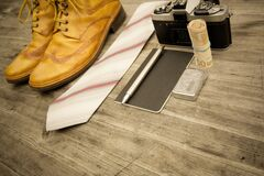 Brown Leather Oxford Wingtip Shoes Beside White and Pink Necktie on Brown Wooden Table Stock Photo