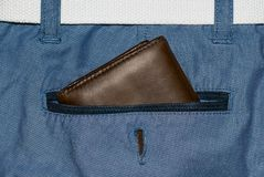 Brown leather purse in the pocket. Wallet halfway out from a jeans back. Pocket blue jeans with Wallet brown Royalty Free Stock Photos