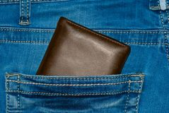 Brown leather purse in the pocket. Wallet halfway out from a jeans back. Pocket blue jeans with Wallet brown Royalty Free Stock Photography
