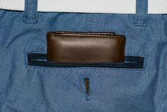 Brown leather purse in the pocket. Wallet halfway out from a jeans back. Pocket blue jeans with Wallet brown Stock Photography
