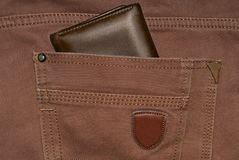 Brown leather purse in the pocket. Wallet halfway out from a jeans back. Pocket jeans with Wallet brown color Stock Photo