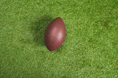 Brown leather rugby ball on green grass. Top view of brown leather rugby ball on green grass Royalty Free Stock Photo