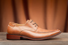 Brown leather shoe for men. Brown leather shoe on a brown background Stock Image