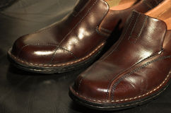 Brown leather shoes on black background. Two brown leather shoes on black leather background Stock Photo