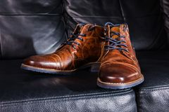 Brown Leather shoes displayed on black leather sofa. A pair of brown men`s leather shoes on black leather sofa Stock Images