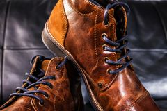 Brown Leather shoes displayed on black leather sofa. A pair of brown men`s leather shoes on black leather sofa Royalty Free Stock Images