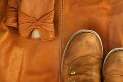 Brown leather shoes and gloves on background of same bag. Two copper-colored boots stand leather bag with a string adornment thread Stock Photography